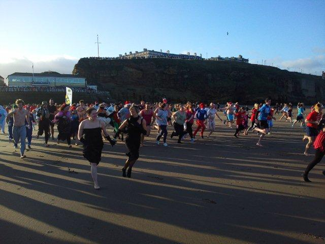 Photo of Boxing Day participants running to the sea